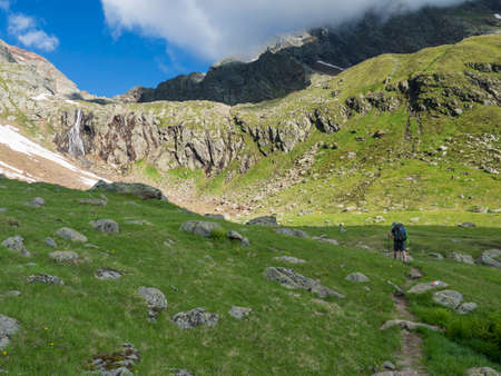 Man hiker with heavy backpack at Stubai hiking trail, Stubai Hohenweg at green summer alpine mountain valley with waterfall. Tyrol, Austrian Alps