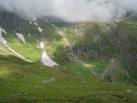 view on green mountain slopes with waterfall from melting snow, summer sunny day with low fog and clouds. Hiking trail, Stubai Hohenweg Tirol, Austrian Alps 免版税图像