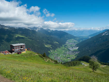 View over green Stubai valley and Neustift im Stubaital village with Elferhutte, grass meadow, moutain peaks and kites. Tirol Alps, Austria, Summer blue sky, white clouds