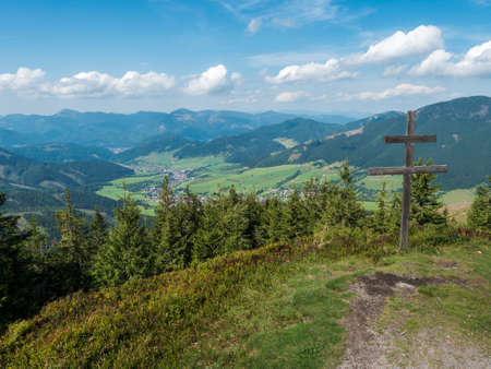 wooden double cross with view on village Liptovska Luzna at ridge of Low Tatras mountains with mountains, hills, meadow and trees. Slovakia, summer sunny day, blue sky white clouds background 免版税图像
