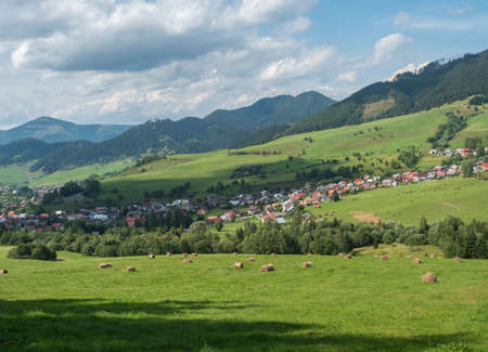 view on village Liptovska Luzna at the foothills of Low Tatras mountains with lush green meadow, forested hills and straw bales. Slovakia, summer sunny day, blue sky white clouds background