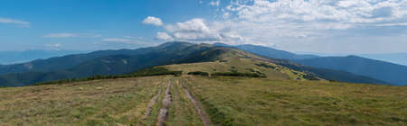 Wide panorama of grassy green hills and slopes at ridge of Low Tatras mountains with hiking trail footpath, mountain meadow, and pine scrub, Slovakia, summer sunny day, blue sky background 免版税图像