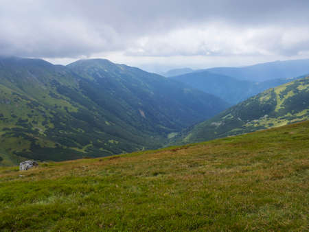 View from grassy hill slopes of hiking trail from Chopok at mountain meadow landscape of ridge Low Tatras mountains Nature park, Slovakia. cloudy late summer day
