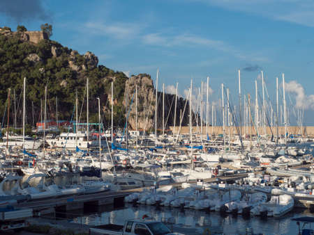 Santa Maria Navarrese, Sardinia, Italy, September 12, 2020: View of marina port of Santa Maria Navarrese with sailing ships, fisherman boats and green hill with rocks. Summer, golden hour light 新闻类图片