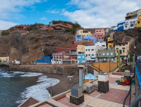 Sardina del Norte, Grand Canaria, Canary islands, Spain, December 13, 2020: view of village Puerto de Sardina del Norte with sand beach, coastal cliffs, marina and colorful houses. Editöryel