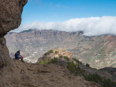 Cruz de Tejeda, Canary Islands, Spain December 15, 2020: Group of tourist hikers sitting at feet of Roque Nublo with view of on central volcanic mountains plateau, Caldera and Barranco de Tejeda Editöryel