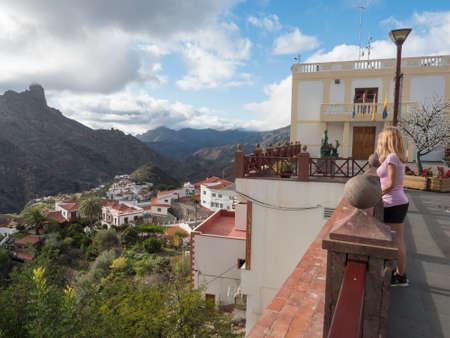 Tejeda, Gran Canaria, Canary Islands, Spain December 15, 2020: Young woman standing in front of town hall, admiring view of Caldera de Tejeda and bentayga rock in picturesque Canarian village. Editöryel