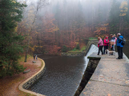 Czech Republic, Nadeje, November 1, 2020: Group of people, family on walk with dog standing on a dam at forest lake with autumn colorful trees at Luzicke hory Lusatian Mountains