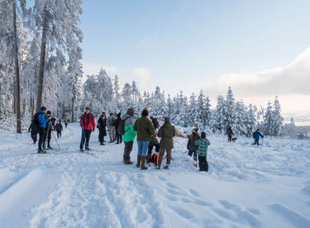 Czech Republic, Brdy mountains, January 9, 2021: Group of people and cross-country skiers on a walk at snowy road in winter forest with snow covered spruce trees