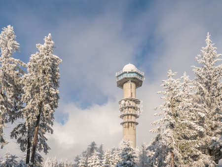 Czech Republic, Brdy mountains, January 9, 2021: View of meteorologic radar tower on top of Praha hill in winter forest with snow covered spruce trees and blue sky