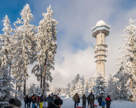 Czech Republic, Brdy mountains, January 9, 2021: Group of people on a walk at snowy road in winter forest with snow covered spruce trees and meteorologic radar tower on top of Praha hill. Editöryel