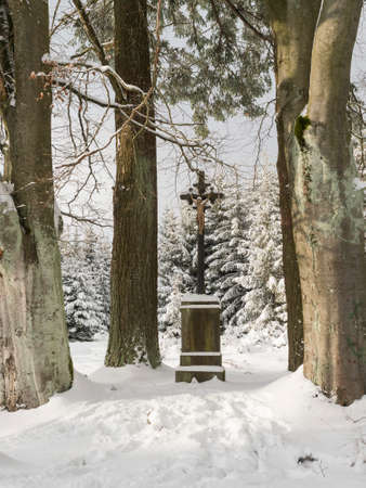 Baroque iron cross on sandstone pedestal with crucifix along snowy path with big beech trees at snow covered spruce tree forest. Brdy Mountains, Hills in central Czech Republic