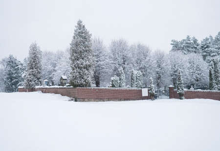 Beautiful winter landscape with view of snowy cemetary at Travnik village surrounded by red brick wall, snow-covered fields and frost tree on cloudy day, white sky background