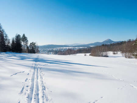 Winter landscape with view of village town Cvikov and ski run trail on snow-covered fields and snowy frozen forest and trees on sunny day, blue sky background