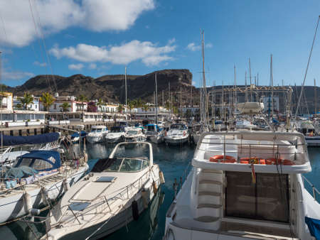 Puerto de Mogan, Gran Canaria, Canary Islands, Spain December 18, 2020: Marina with sailing ships and boats and colorful buildings at small fishing village Puerto de Mogan, favorite tourist place. Editorial