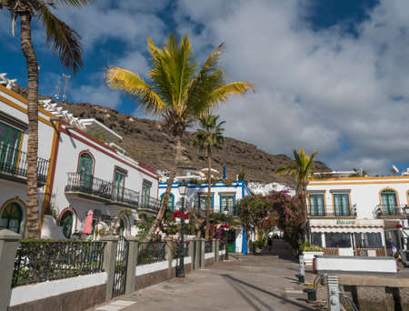 Puerto de Mogan, Gran Canaria, Canary Islands, Spain December 18, 2020: Traditional colorful houses at pedestrian street of small fishing village port Puerto de Mogan, favorite tourist place.