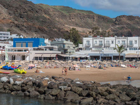 Puerto de Mogan, Gran Canaria, Canary Islands, Spain December 18, 2020: View on the public beach with golden sand and apartments in popular holiday village Puerto de Mogan at sunny day