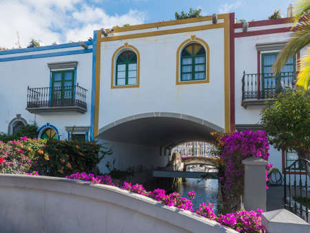 Colorful buildings of Puerto de Mogan with sea canal and boat and flowers. Traditional colonial architecture of small fishing village port, favorite tourist place. Gran Canaria, Canary Islands, Spain Archivio Fotografico