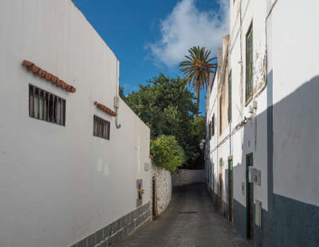 Narrow street in Agaete city center with traditional architecture, old white houses in colonial style, stone wall and tropical garden with palm trees. Gran Canaria, Canary Islands, Spain Imagens