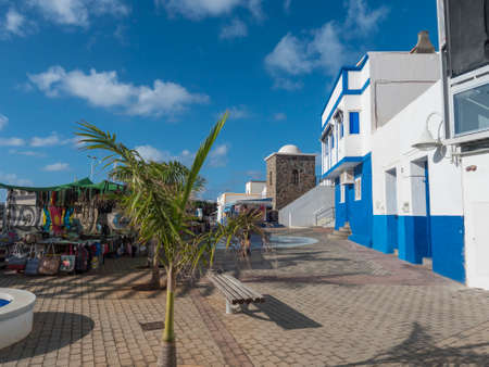 Puerto de las Nieves, Agaete, Gran Canaria, Canary Islands, Spain December 17, 2020: Main street at fishing village with market stands, traditional blue white houses and palm tree