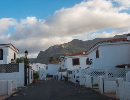 Luxury holiday apartments, white houses at hill above Puerto de las Nieves, popular seaside resort with view of Tamadaba green mountains. Agaete, Gran Canaria, Canary Islands, Spain