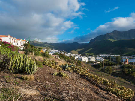 View over white houses amd apartments of Agaete city, popular seaside resort with view of Tamadaba green mountains.Gran Canaria, Canary Islands, Spain Imagens