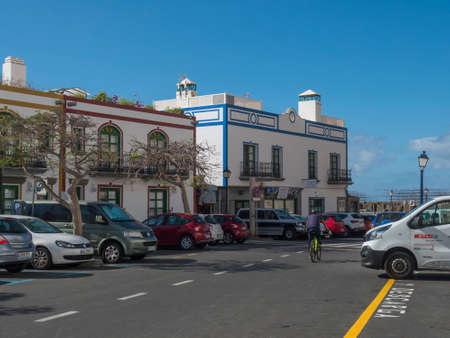 Puerto de Mogan, Gran Canaria, Canary Islands, Spain December 18, 2020: Car parking at main road leading to port with traditional colorful houses, street of Puerto de Mogan, favorite tourist place. Editorial