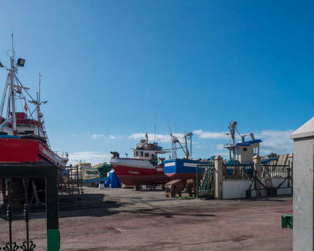 Puerto de Mogan, Gran Canaria, Canary Islands, Spain December 18, 2020: View of dry dock where ships and boats are repaired with two maintenance man at small fishing village port Puerto de Mogan