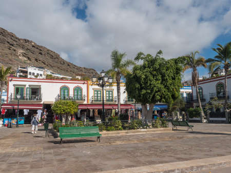 Puerto de Mogan, Gran Canaria, Canary Islands, Spain December 18, 2020: Traditional colorful houses at pedestrian street with souvenir and clothes shops at port Puerto de Mogan, popular tourist resort