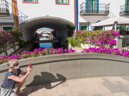Puerto de Mogan, Gran Canaria, Canary Islands, Spain December 18, 2020: Senior woman in face mask takes picture of street with colorful houses, canals and flowers at Puerto de Mogan, tourist resort