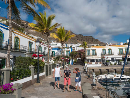 Puerto de Mogan, Gran Canaria, Canary Islands, Spain December 18, 2020: Group of tourist at pedestrian street of port Puerto de Mogan, popular resort with colorful traditional colonial houses Editorial