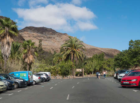 San Bartolome de Tirajana, Gran Canaria, Canary Islands, Spain December 18, 2020: Cars and parking lot at entrance to Zoo Palmitos park with three tourist woman, sunny day