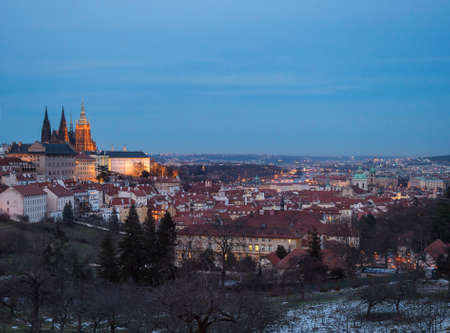 Evening view of illuminated St. Vitus Cathedral gothic churche and Prague Castle panorama, hradcany and Mala Strana quarter from Petrin hill, blue sky background Imagens