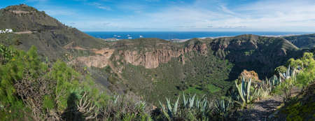 Panoramic view of volcanic landscape of Caldera de Bandama crater and Pico de Bandama with circular hiking trail. Gran Canaria, Spain. Sunny day, blue sky. Imagens