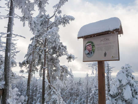 Czech Republic, Brdy mountains, January 9, 2021: View of signboard with info text about writer Jan Caka at viewpoint named by him. Winter forest landscape with snow covered spruce trees and branches Editorial