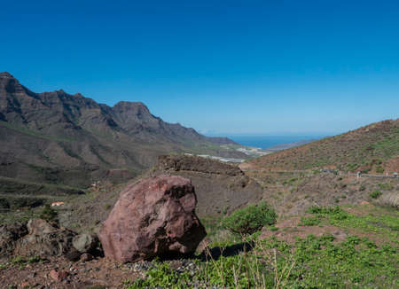 view of rocky mountains and green valley with big red rock. Landscape in the north west of Gran Canaria. Clear blue sky