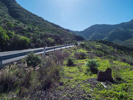 view of winding road at rocky mountains and green hills. North west Gran Canaria landscape. Clear blue sky Foto de archivo