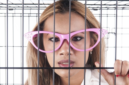 Blonde asian girl with funny glasses  in a cage Stock Photo - 19691853