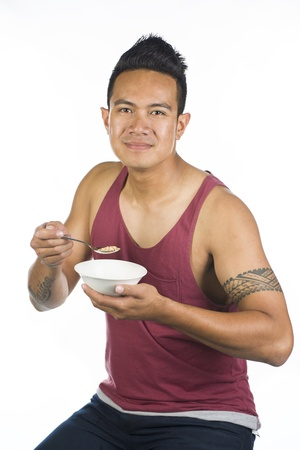 A Polynesian guy against a white background with a bowl of serial