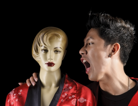A studio photograph of an Asian guy shouting at a mannequin Stock Photo