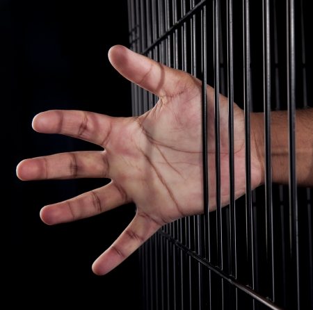 A Middle Eastern guy locked up in a black cage