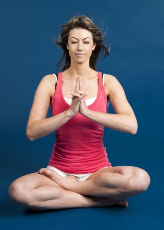woman doing yoga against a blue background photo