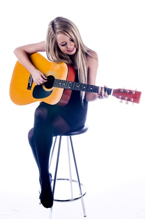 a blonde guitar player tuning her guitar
