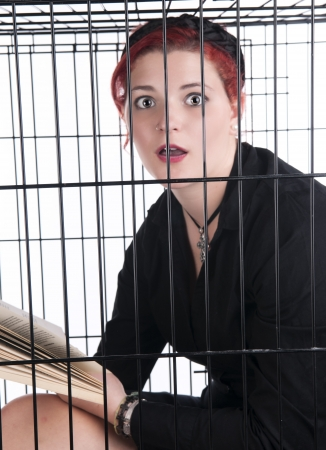 An image of a Caucasian girl with red hair in a cage against a white background Stock Photo - 20685172