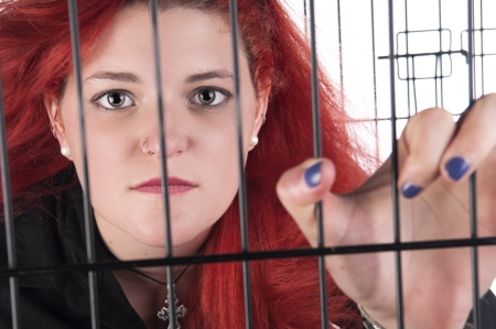 An image of a Caucasian girl with red hair in a cage against a white background Stock Photo - 20707582