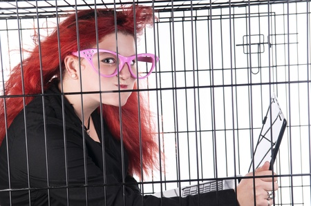 An image of a Caucasian girl with red hair in a cage against a white background photo