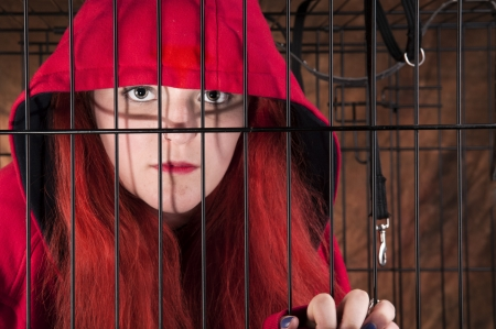 An image of a Caucasian girl with red hair in a cage against a brown background Stock Photo - 20707412