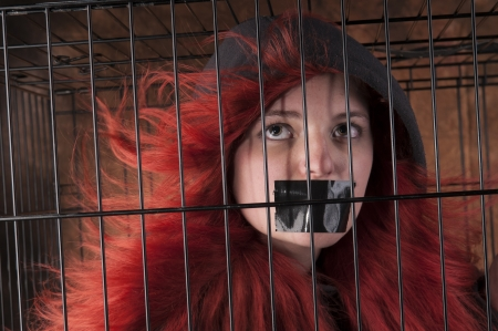 An image of a Caucasian girl with red hair in a cage against a brown background Stock Photo - 20707422