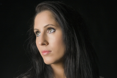 A Caucasian woman with black hair against a black background