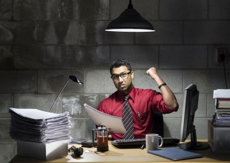 An image of an Indian businessman with a red shirt and tie behind a desk in a basement office